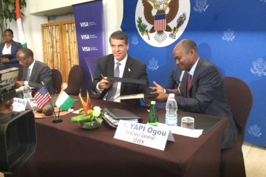 USTDA's Director, Congressional and Public Affairs (left) signs the grant with Mr. Yapi Ogou, Director General, SODEN. Photo by USTDA.
