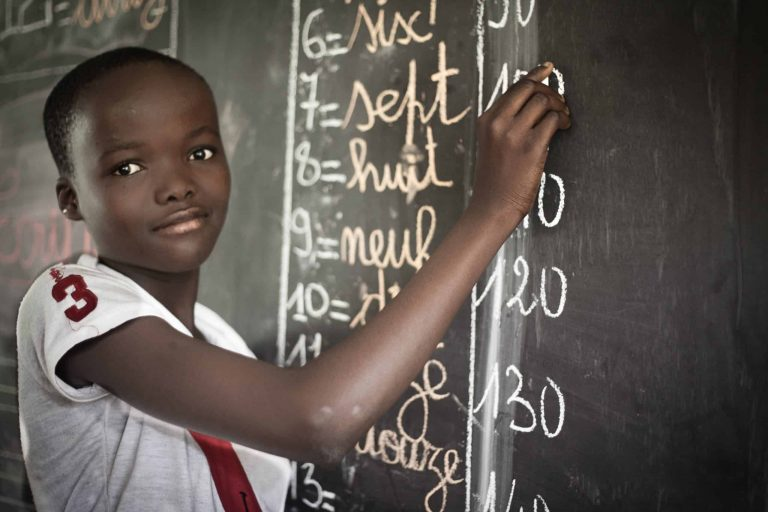 Photo of girl child writing on blackboard in school in a cocoa growing community in West Africa