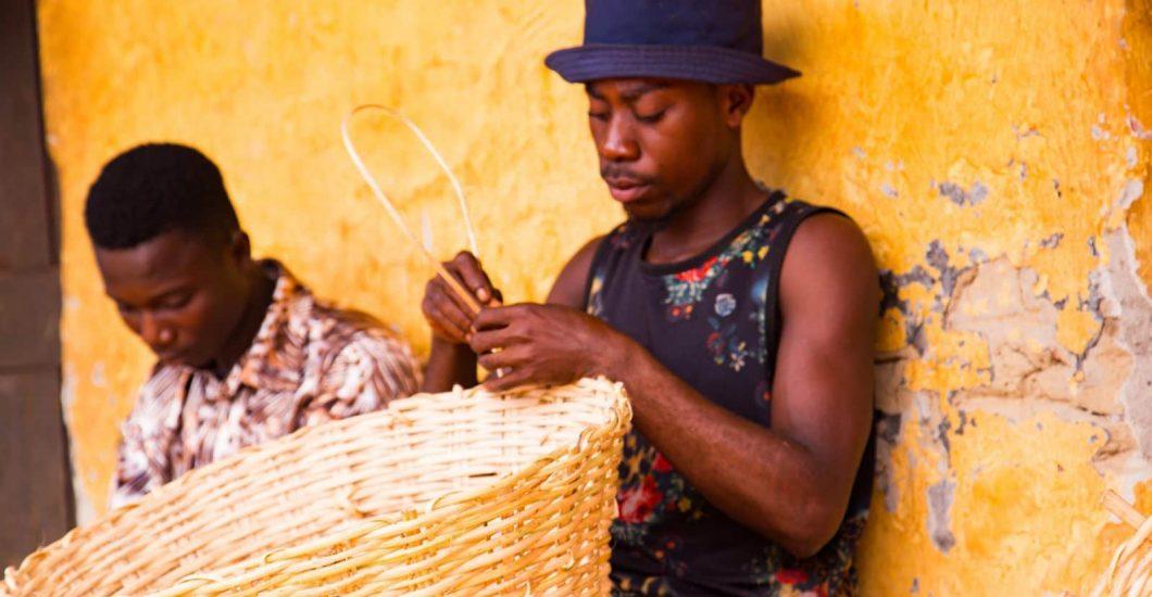 A cocoa community member weaves a basket in Nyamebekyere, Ashanti region, Ghana