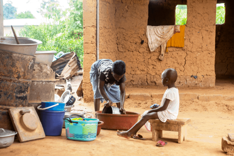 West African mother and child washing a pot near their home
