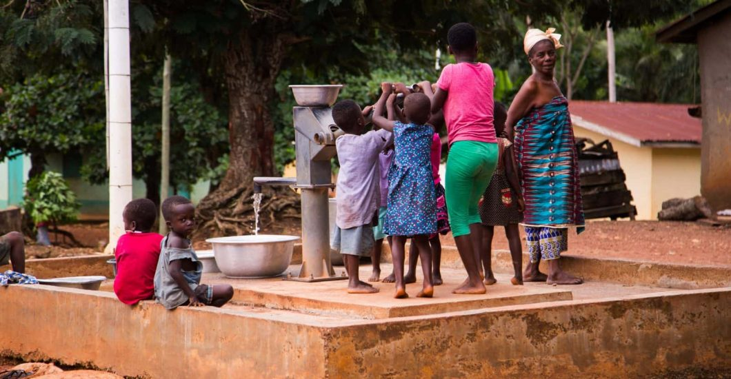 Community members are pumping water at a well in Nyamebekyere, Ashanti region, Ghana