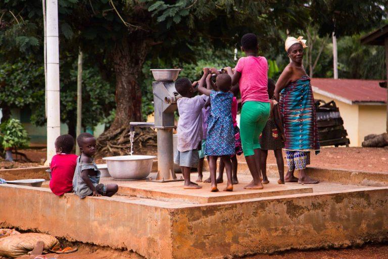 Community members are pumping water at a well in Nyamebekyere, Ashanti region, Ghana