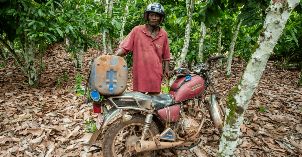 Cocoa farmer and motorcycle on sustainable cocoa farm