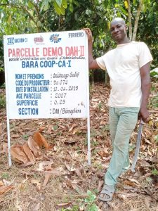 Sustainable cocoa farmer Ouedrago Salif standing by coop sign in Cote dIvoire