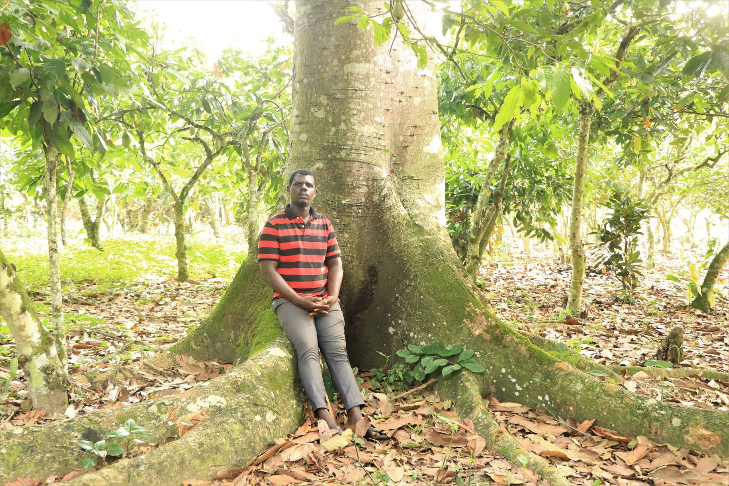 Sustainable cocoa farmer Isaac Boafo stands by tree on sustainable cocoa farm