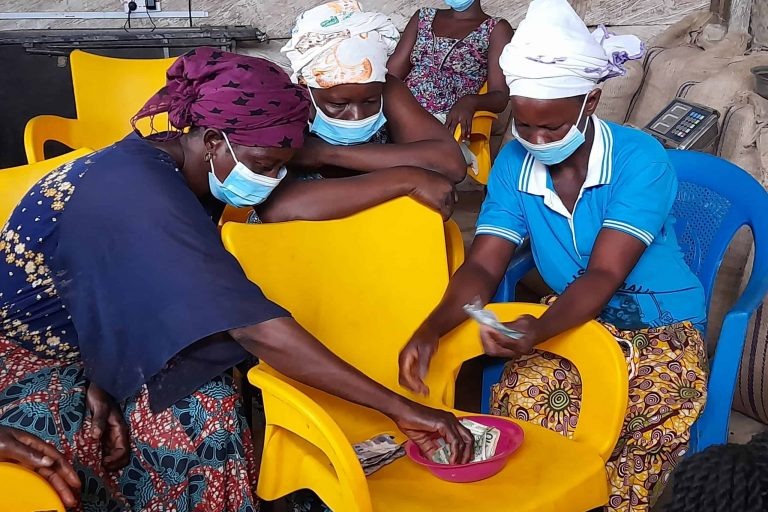 Savings group members accounting for their day's contribution at Wawase in Ghana