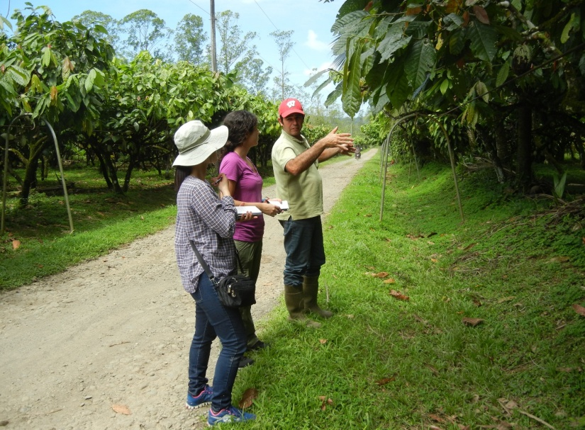A farmer explaining climate change impacts on cocoa production to GWU students, Ana Tamargo and Yeongmi Kim. (Picture by Oscar Brenes)